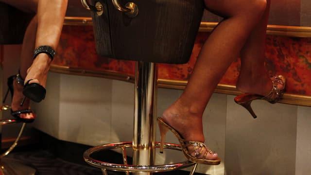 Beine von Prostituierten in einer Bar.