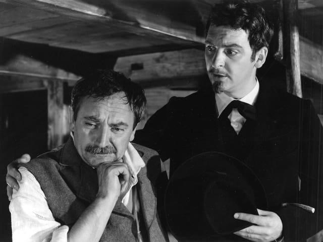 Ein Mann schaut traurig und gebannt nach unten (zum Bett). Neben ihm steht ein Arzt, der seine rechte Hand um die Schulter des anderen Mannes gelegt hat.