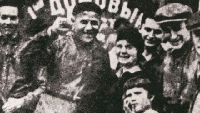 Alte Fotografie zeigt einen Mann mit erhobener Faust in einer Gruppe Menschen.