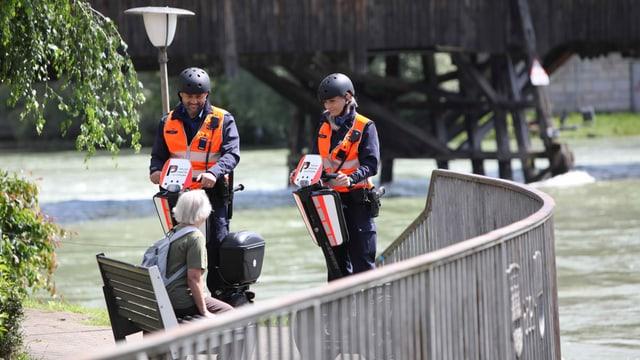 Zwei Beamte auf Segways sprechen mit einer Passantin auf einer Parkbank