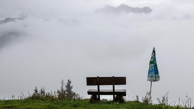 Eine Sitzbank und ein zugeklappter Sonnenschirm vor trüber Aussicht auf das verregnete und nebelverhangene Bergpanorama