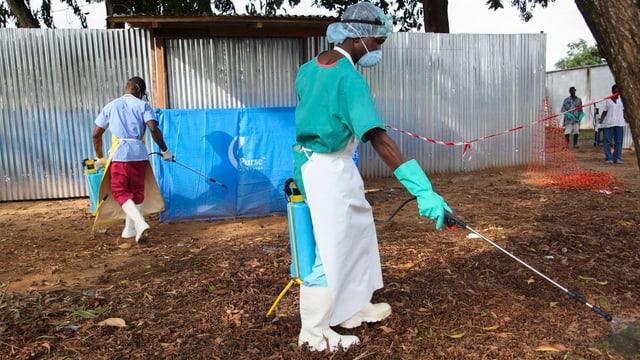 Pfleger versprühen Desinfektionsmittel in Monrovia (Liberia).