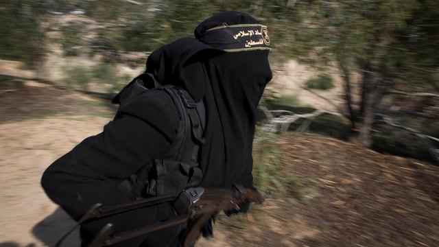 Eine Frau in schwarz, total verhüllt, mit einem Dschihad-Stirnband und einer Waffe.