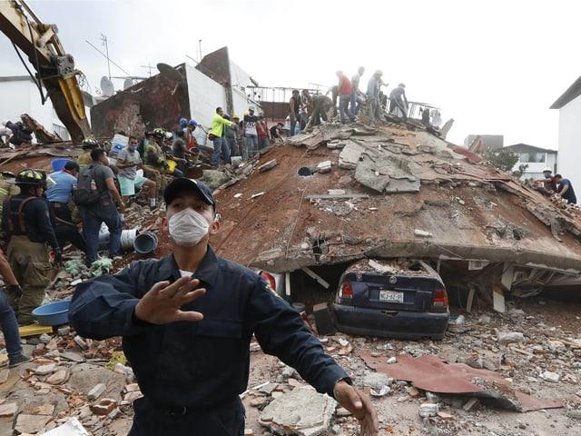 Mann mit Staubmaske im Vordergrund, dahinter ein zusammengebrochenes Gebäude.