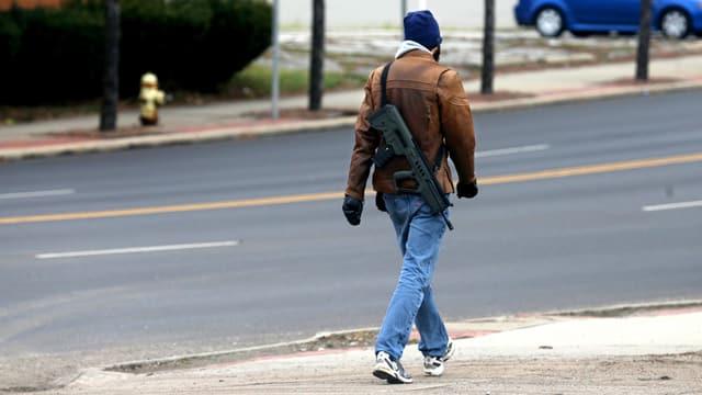 Mann von hinten, der mit einer Seriefeuerwaffe durch die Strassen spaziert.