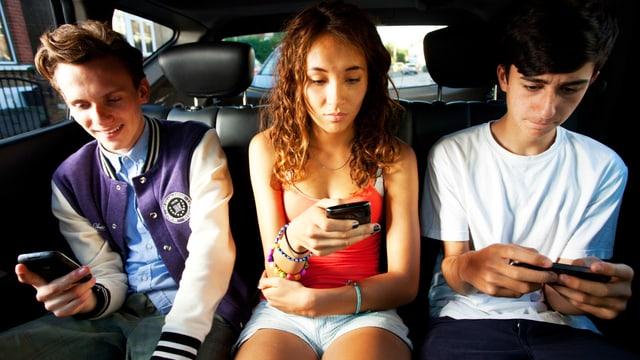 Drei junge Menschen in einem Auto. Sie spielen alle auf ihren Smartphones.