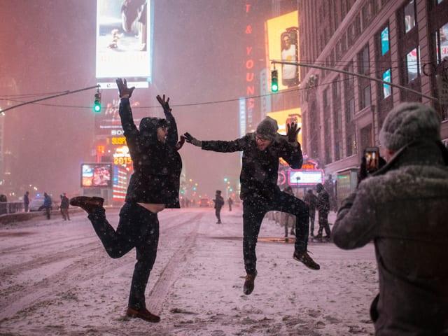 Männer springen am Times Square herum.