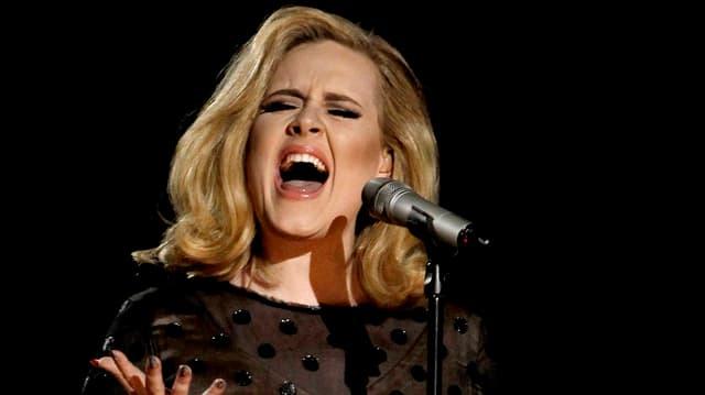 Adele am Mikrofon stehend und singend.