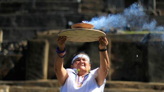 Vor einer archäologischen Städte hält eine Frau eine Schale mit Feuer in die Luft.