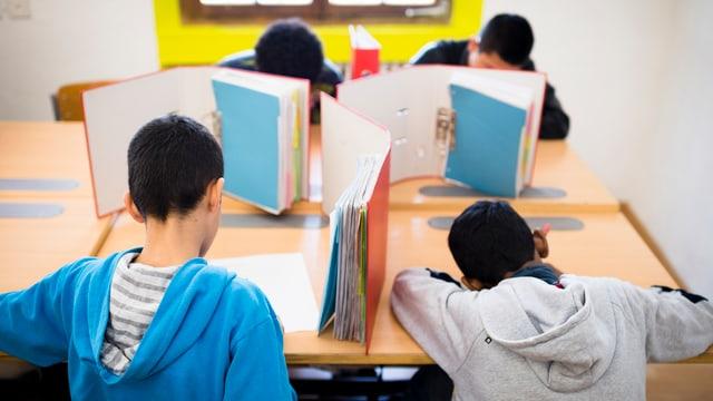Requirents d'asil minorens en situaziun da scola en il center transitoric a Tavau.