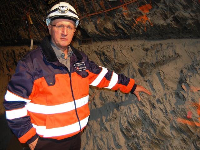 Mont Terri-Laborleiter Paul Bossart vor einer wunderschön geschichteten, dunkelgrauen Opalinuston-Schicht im Felslabor.