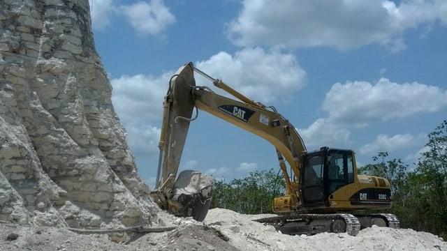 Ein Bagger gräbt Steine ab.