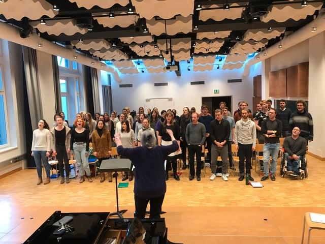 Etwa 50 Chormitglieder singen zusammen. Vorne eine Dirigentin.