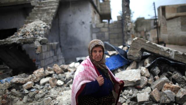 Eine syrische Frau steht in Häuserruinen. Sie macht einen apathischen Eindruck.
