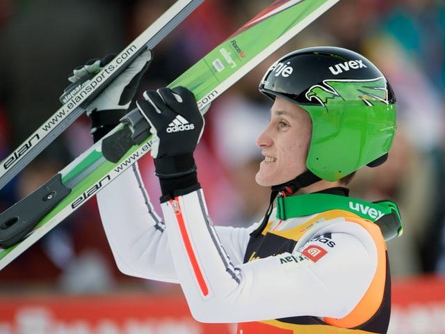 Peter Prevc hält die Skier hoch.