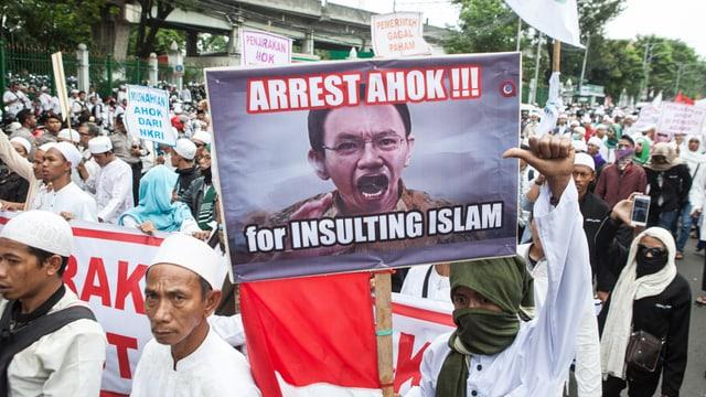 Muslime mit weissen Kappen tragen ein Transparent mit einem Foto von Basuki und der Aufschrift: «Verhaftet ihn, weil er den Islam beleidigt hat.»
