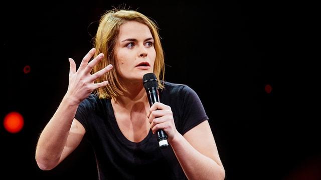 Frau mit Mikrofon, gestikulierend auf einer Bühne stehend.