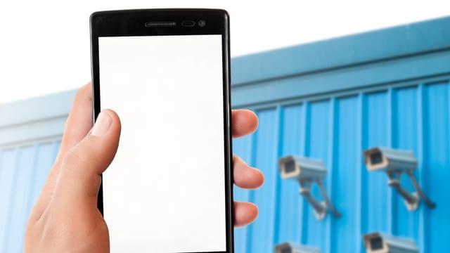 Eine Hand hält ein Handy, im Hintergrund sind vier Überwachungskameras an einer Wand montiert.
