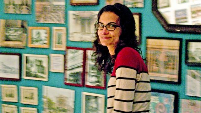Die Hala Elkoussy steht vor einer Wand, an der zahlreiche Bilder in verschiedenen Formaten hängen.
