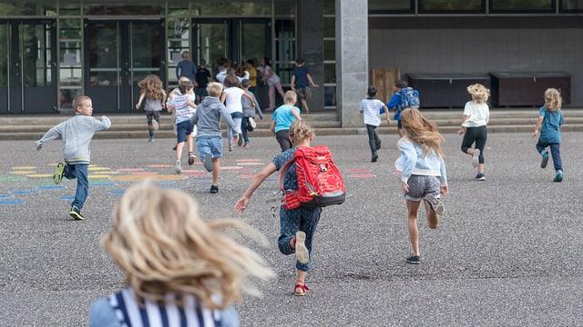 Schüler rennen über einen Pausenhof.