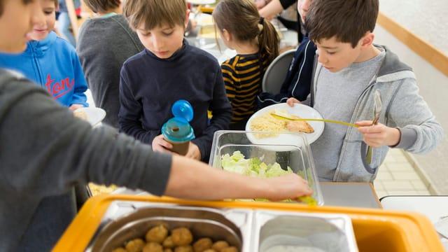 Kinder essen Zmittag in der Schule.