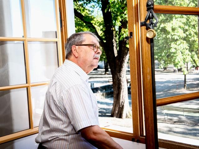 Ein älterer Herr mit Brille und Schnauz schaut aus dem geöffneten Fenster.