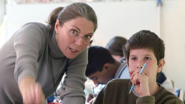 Eine Lehrerine im grauen Pullover mit Brille zeigt auf die Kamere, daneben ein Schüler mit blauem Bleistift in der Hand.