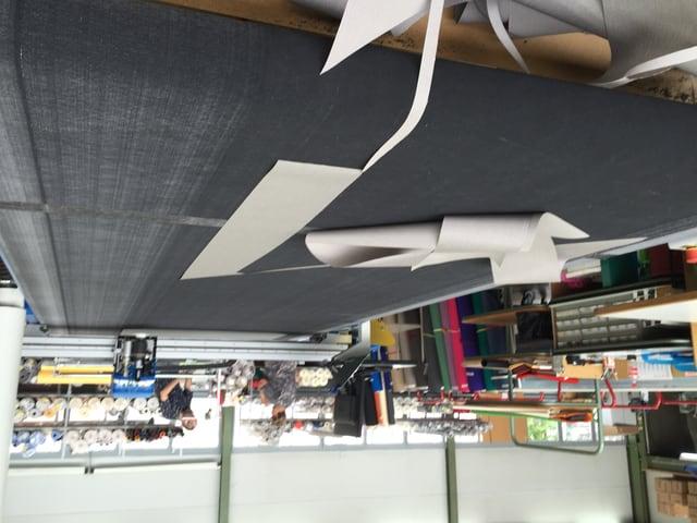 Eine Maschine schneidet die Stoffe für die Sonnenschirme zu.