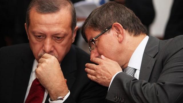 Davutoglu flüstert Erdogan etwas ins Ohr.
