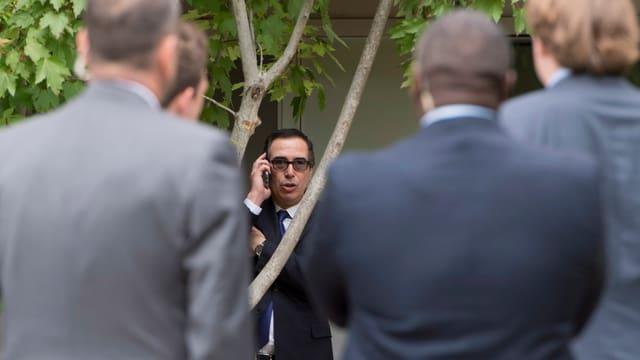 US-Finanzminister Steven Mnuchin am Telefon, umringt von Sicherheitskräften.