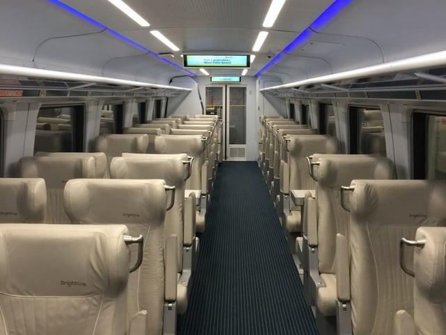 Ein leerer Zugwaggon, ohne Passagiere. Die crémefarbenen Sitze aus Kunstleder sehen neu aus. An der Decke glimmen nebst dem normalen Licht blaue Neonröhren.