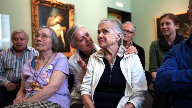 Menschen sitzen in Stühlen im Museum vor Kunstwerk