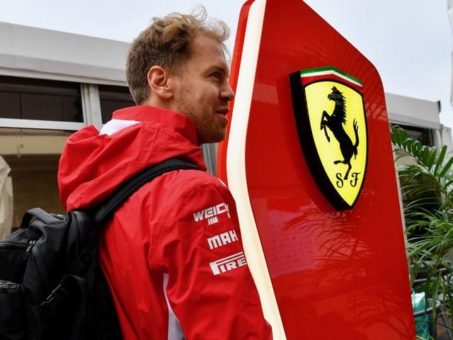 Sebastian Vettel vor einem Ferrari-Logo