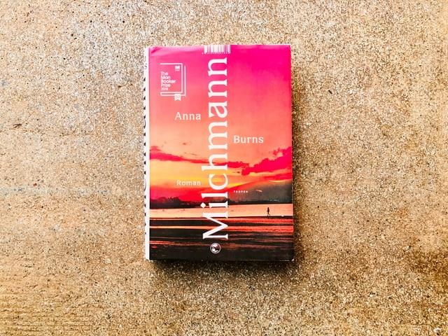 Der Roman «Milchmann» von Anna Burns liegt auf einem grauen Zementboden
