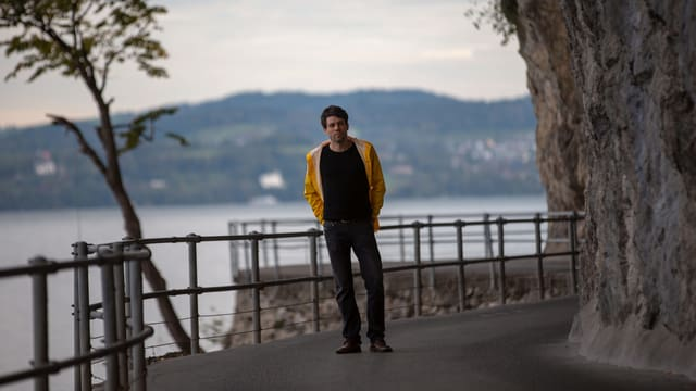 Ein Mann steht am Seeufer