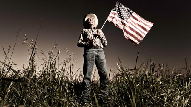 Ein älterer Cowboy steht mit einer US-Flagge in der Hand auf einer Wiese.