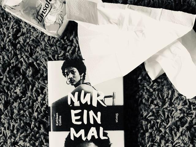 Der Erzählband von Kathleen Collins: «Nur einmal» liegt auf einem Teppich, zerknüllte Nastücher daneben