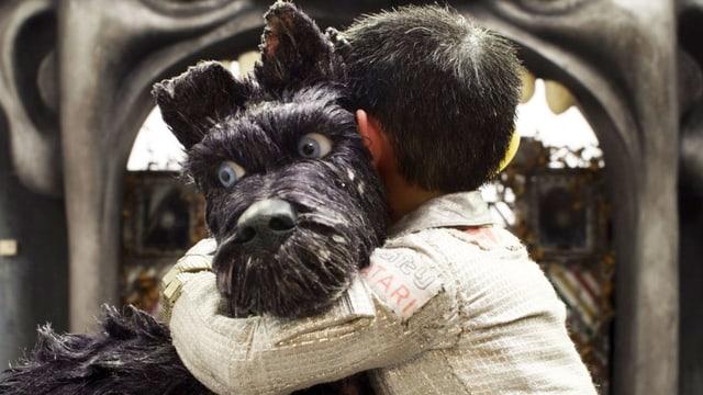 Ein Junge umarmt ein Hund