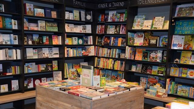 Eine Buchhandlung mit schwarzen Gestellen voller farbiger Bücher, in der Mitte ein heller Holztisch.