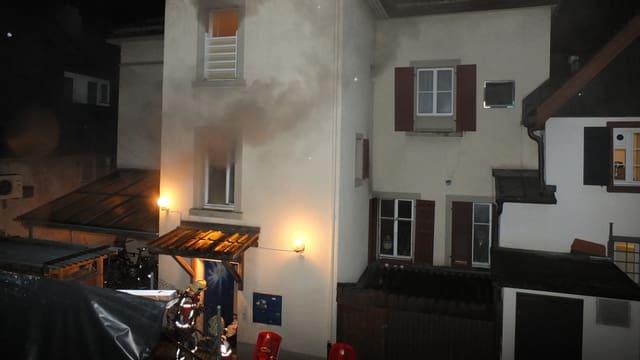 Rauch dringt aus dem Fenster eines Hauses.