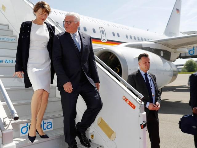 Frank-Walter Steinmeier und seine Frau Elke Buedenbender schreiten die Flugzeugtreppe herunter.