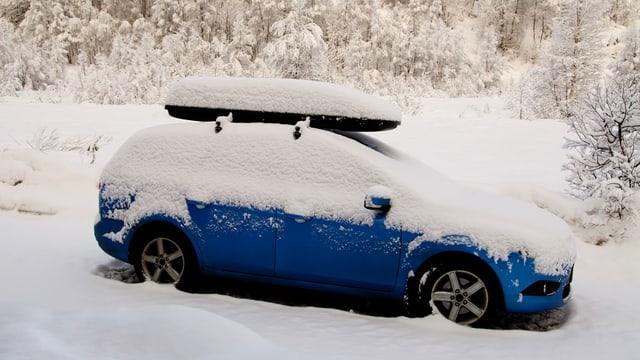 Blaues, schneebedecktes Auto mit Dachbox