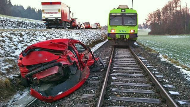 Demoliertes Auto neben dem Bahngleis