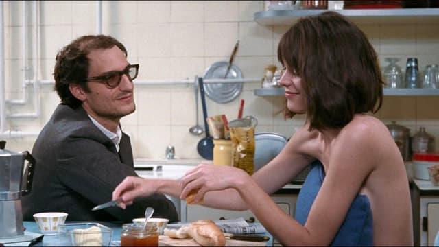 FIlmstill: Ein Mann und eine Frau sitzen an einem Tisch.
