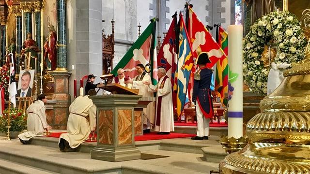 Chor einer Kirche mit Priester und Fahnen