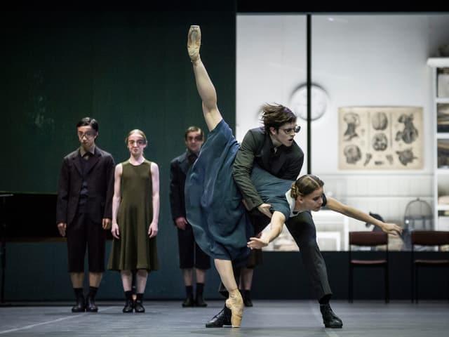 Eine Tänzerin, den Oberkörper gegen den Boden geneigt, und ein Tänzer mit wirren Haaren.