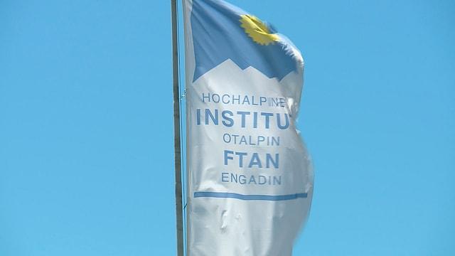 Bindera cun logo da l'Institut Otalpin a Ftan
