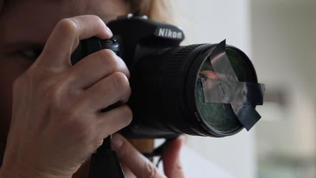 Ein Fotograf hat eine Linse vor dem Fotoapparat abgeklebt.