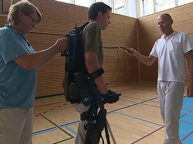 Ein Patient, der mit Hilfe eines Laufroboters und Physiotherapeuten aufrecht geht.