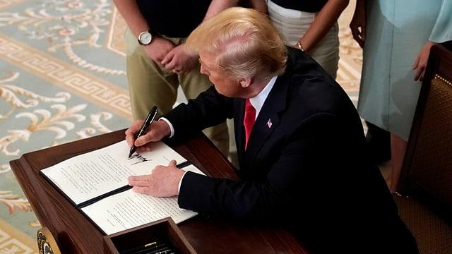 Purtret da Trump co el suttascriva in document.